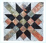 Railroad Crossing, a nine patch quilt block, made of two batiks and a printed cotton.   There is a new one each month.  Please join us. Directions to the website are on our home page.