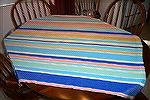 Full view of tablecloth woven by Ramona Abernathy-Paine. Fibinacci numbers used to determine stripe width and spacing. Colors come from Fiesta Ware. Woven of Orlec.